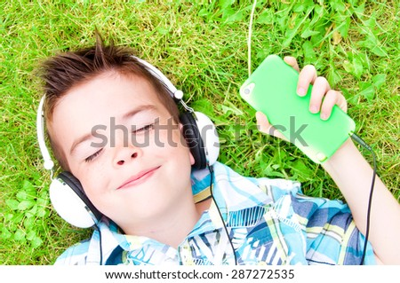 Child listening to music with headphones and smart phone lying on grass - stock photo
