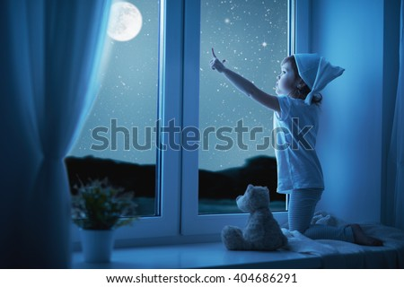child little girl at the window dreaming and admiring the starry sky at bedtime night - stock photo
