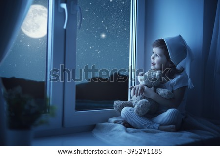 child little girl at the window dreaming the starry sky at bedtime night - stock photo