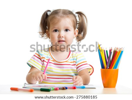 child little girl draws with pencils sitting at table - stock photo