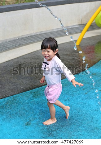 Child little girl having fun to play with water in park fountain