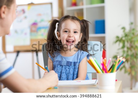 Child little girl laughing, painting colorful pencils at her playtable - stock photo