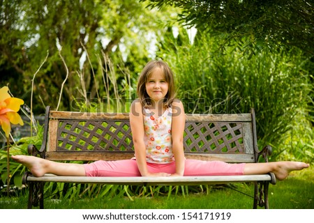 Child (little girl) performing gymnastic pose on bench outdoor in backyard - stock photo
