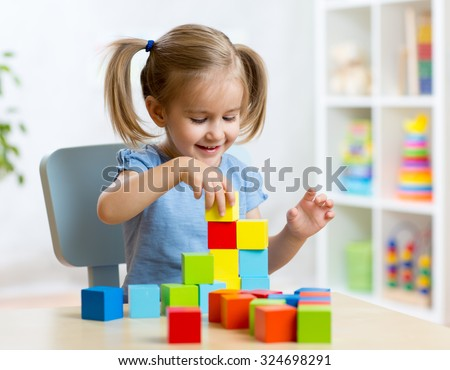 child little girl playing wooden toys at home or kindergarten - stock photo