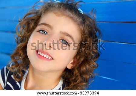 child little girl smiling portrait on wooden blue wall - stock photo