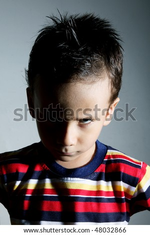 Child looking angry at the camera over gray background