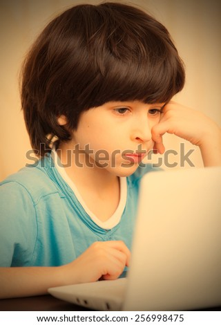 child looking at a computer monitor, distance learning. instagram image retro style - stock photo