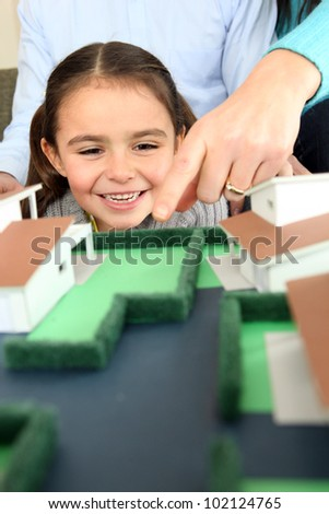 Child looking at a model of a housing estate - stock photo