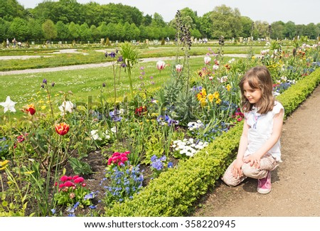 Child looking at flower beds in springtime - stock photo