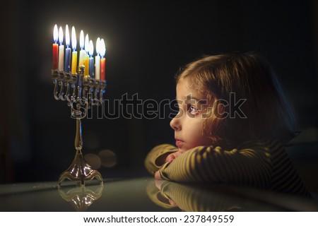 Child Looking at Menorah Candles - stock photo