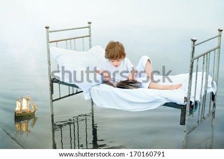 Child looking at old album on vintage bed in water on sea shore - stock photo