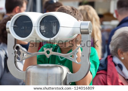 Child looking inside a tourist binoculars next to the sea in Trieste - stock photo