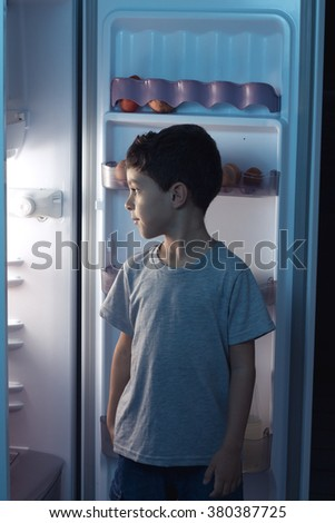 Child looking into the refrigerator in the middle of the night