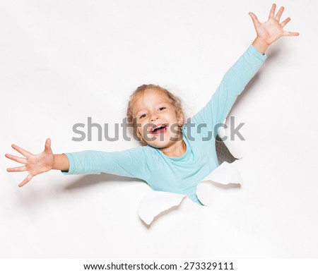 Child looking out of a hole. Banner. Happy girl - stock photo