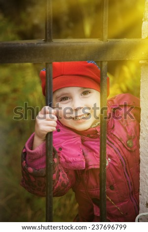 Child looking out of locked wire fencing. outdoors - stock photo