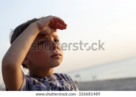 Child looking out with hand over eyes - stock photo