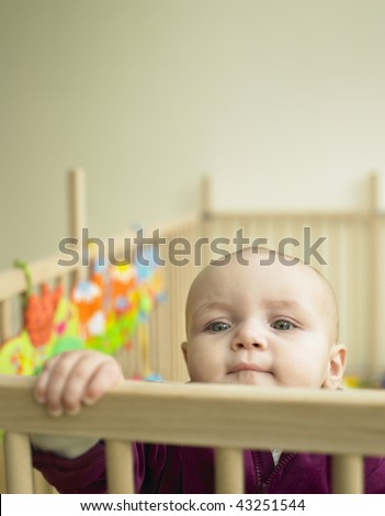 Child looking over the top of playpen. Vertically framed shot. - stock photo