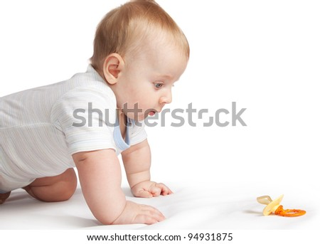 Child looking the pacifier isolated on white background