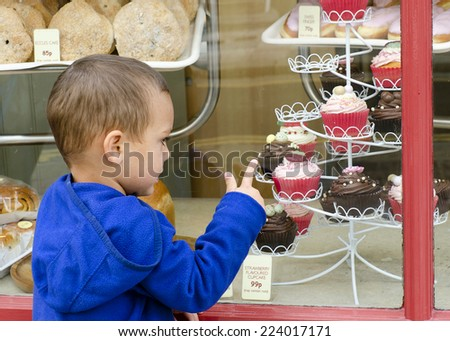 Child looking through the window into sweet cake shop or bakery pointing to cakes.