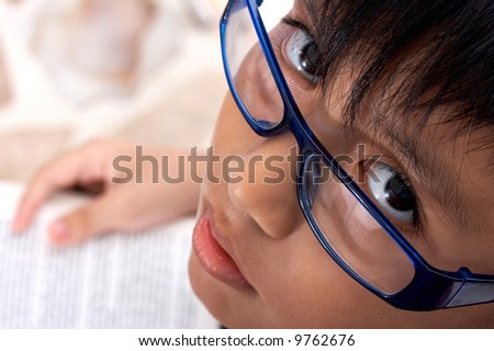 child looking up wearing glasses and holding a book
