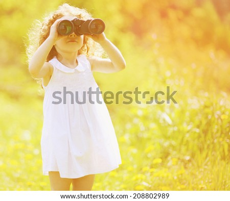 Child looks in binoculars in sunny summer day - stock photo