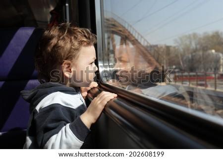 Child looks through the window of the train - stock photo