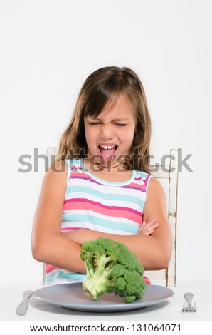 Child looks with disgust at vegetable, refusing to eat it and sticking tongue out - stock photo