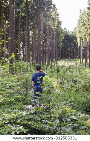 Child lost in deep forest, standing on a tree trunk, back view. - stock photo