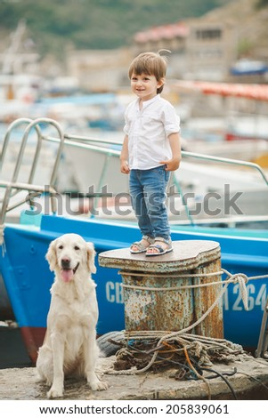 Child lovingly embraces his pet dog. Child walking alone with her lovely dog at beach - stock photo