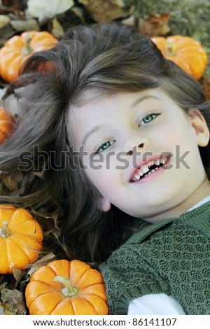 Child lying in autumn leaves and pumpkins. - stock photo