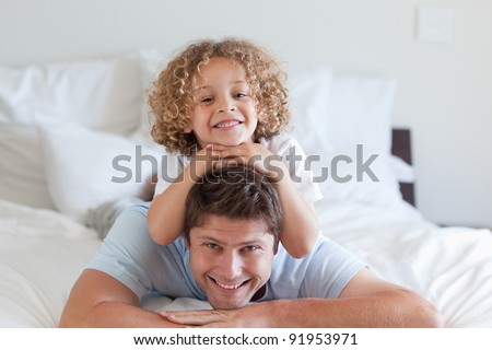 Child lying on fathers back in bed - stock photo