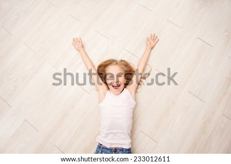 Child lying on floor heating. Girl on laminate, PVC tile - stock photo