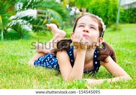Child lying on grass, thinking and dreaming - stock photo