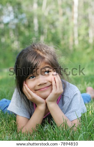 Child lying on grass with a thouhtful expression. Part asian, scandinavian background. - stock photo