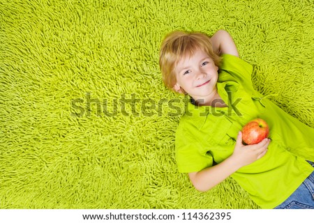 Child lying on the green carpet background, holding apple. Boy smiling and looking at camera - stock photo
