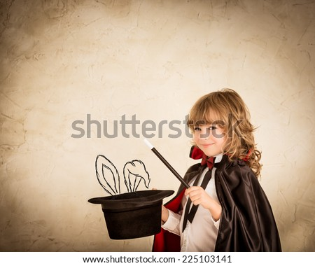 Child magician holding a top hat with drawn rabbit against grunge background - stock photo