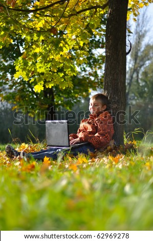 Child make fun with notebook under tree in autumn forest - stock photo