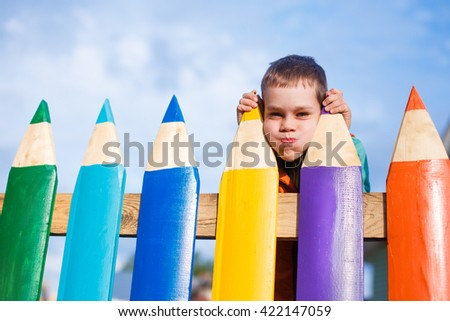 child makes faces behind the fence of pencils. boy making fun of someone through the fence - stock photo