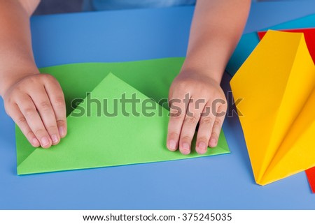 Child making a green paper plane. Close up. - stock photo