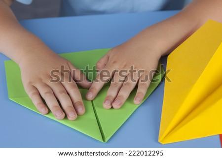 Child making a paper plane. - stock photo