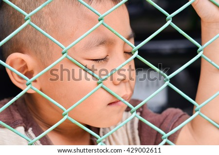 Child making a sad face.boy sad standing alone behind jail.,Handsome boy Close your eyes with a sad face. Sad Asia boy Portrait outdoor