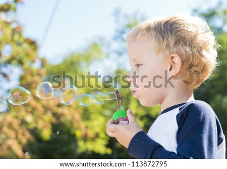 Child making soap bubbles outside