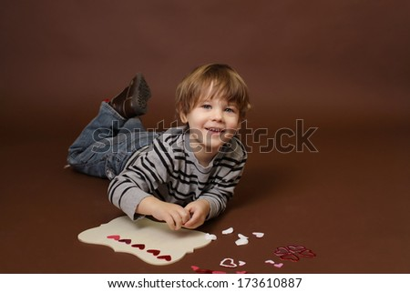 Child making  Valentine's Day Craft with Heart stickers