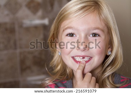 Child missing front tooth pointing at it with her finger