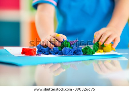 Child moulds from plasticine on table. hands with plasticine. - stock photo