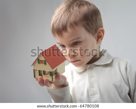 Child observing the model of a house - stock photo