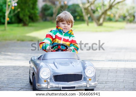 Child of 3 years driving big toy old vintage car and having fun, outdoors. Active leisure with kids outdoors  on warm spring or autumn day. - stock photo
