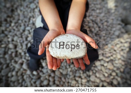 Child on a beach with hands cupped holding stone pebble with the word hope engraved concept for faith, love, spirituality and religion - stock photo