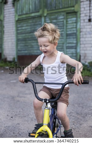 Child on a bicycle at asphalt road. Childhood. Sport. Cycling - stock photo
