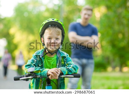child on a bicycle with father in the park - stock photo